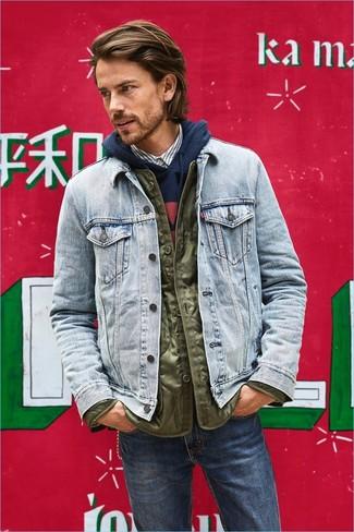 Come indossare e abbinare: piumino leggero verde oliva, giacca di jeans azzurra, felpa con cappuccio stampata blu scuro, camicia a maniche lunghe a righe verticali bianca