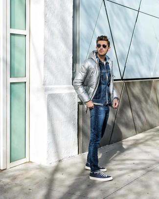 Come indossare e abbinare: piumino argento, giacca di jeans blu scuro, t-shirt girocollo a righe orizzontali bianca, jeans blu scuro