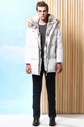 Come indossare e abbinare: piumino lungo bianco, maglione girocollo grigio scuro, chino neri, scarpe derby in pelle nere