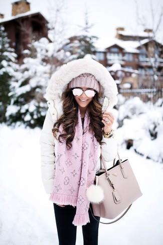 Come indossare e abbinare: piumino lungo bianco, jeans aderenti neri, borsa shopping in pelle rosa, cuffia lavorato a maglia rosa