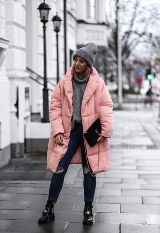 Come indossare: piumino lungo rosa, maglione con scollo a cappuccio grigio, jeans aderenti strappati blu scuro, stivaletti in pelle tagliati neri