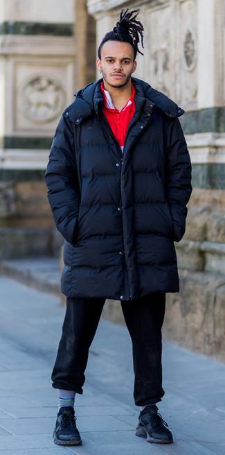 Come indossare e abbinare: piumino lungo blu scuro, maglione con zip rosso, jeans neri, scarpe sportive nere