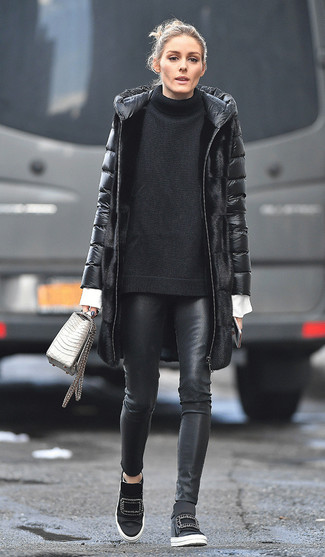 Come indossare e abbinare: piumino lungo nero, maglione oversize lavorato a maglia nero, camicia elegante bianca, pantaloni skinny in pelle neri