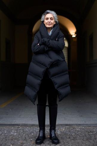 Come indossare e abbinare: piumino lungo nero, leggings neri, stivali al ginocchio in pelle neri