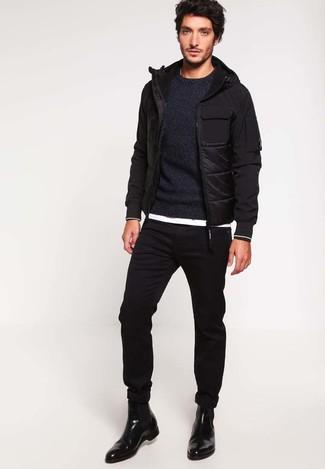 Come indossare: piumino nero, maglione girocollo nero, t-shirt girocollo bianca, jeans aderenti neri