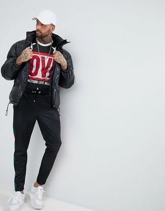 Come indossare: piumino nero, t-shirt girocollo stampata nera, pantaloni sportivi neri, scarpe sportive bianche