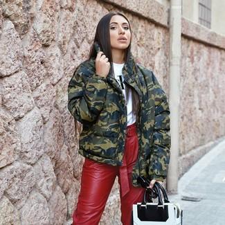 Come indossare: piumino mimetico verde oliva, t-shirt girocollo stampata bianca e nera, pantaloni stretti in fondo in pelle rossi, borsa shopping in pelle bianca e nera