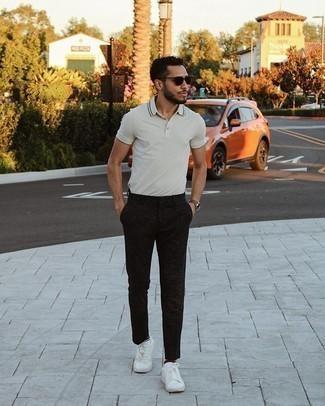Trend da uomo 2021: Coniuga un polo grigio con chino neri per un look spensierato e alla moda. Sneakers basse di tela bianche sono una validissima scelta per completare il look.