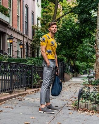 Come indossare e abbinare: polo stampato giallo, pantaloni eleganti scozzesi grigi, scarpe derby di tela grigie, borsa shopping di tela blu scuro