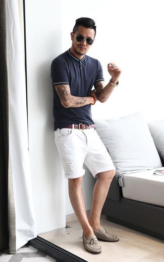 Come indossare e abbinare: polo blu scuro, pantaloncini di jeans strappati bianchi, mocassini con nappine in pelle grigi, cintura in pelle marrone