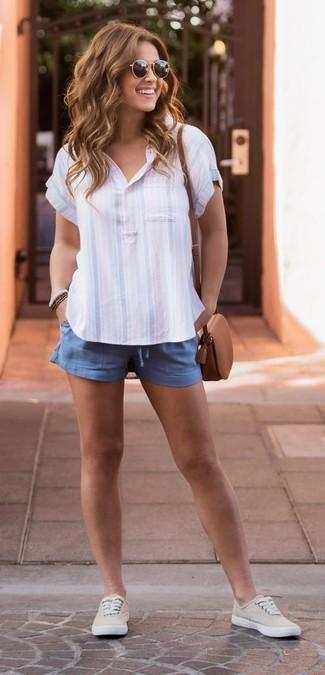 Moda ragazza adolescente in modo casual: Indossa un polo a righe verticali azzurro e pantaloncini blu per creare un look raffinato e glamour. Questo outfit si abbina perfettamente a un paio di sneakers basse di tela beige.