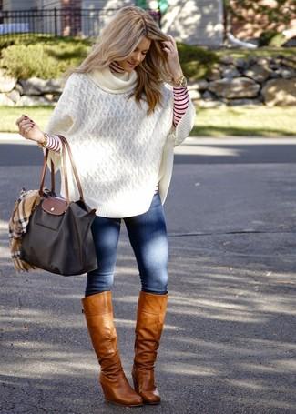 Come indossare e abbinare: poncho lavorato a maglia bianco, dolcevita a righe orizzontali rosso e bianco, jeans aderenti blu, stivali al ginocchio in pelle marrone chiaro