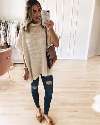 Come indossare e abbinare: poncho beige, jeans aderenti strappati blu scuro, mocassini con nappine in pelle scamosciata marroni, cartella in pelle marrone