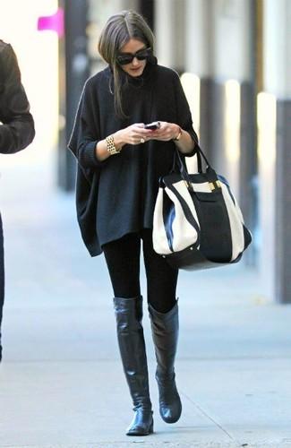 Come indossare: poncho grigio scuro, leggings neri, stivali sopra il ginocchio in pelle neri, borsa shopping in pelle bianca e nera