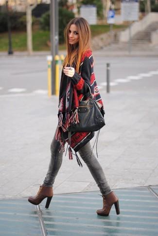 Come indossare: poncho stampato nero, jeans aderenti grigi, stivaletti con lacci in pelle marroni, borsa shopping in pelle nera
