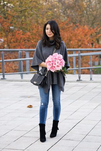 Come indossare e abbinare: poncho grigio scuro, t-shirt girocollo bianca, jeans aderenti strappati blu, stivaletti in pelle scamosciata neri