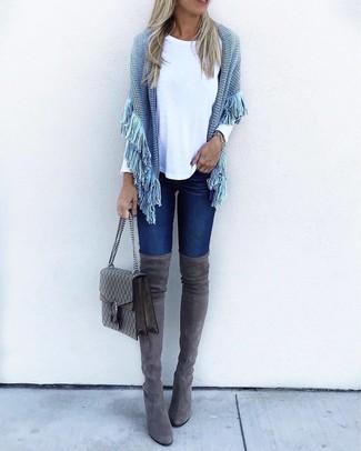 Come indossare e abbinare: poncho lavorato a maglia azzurro, t-shirt manica lunga bianca, jeans aderenti blu scuro, stivali sopra il ginocchio in pelle scamosciata grigio scuro