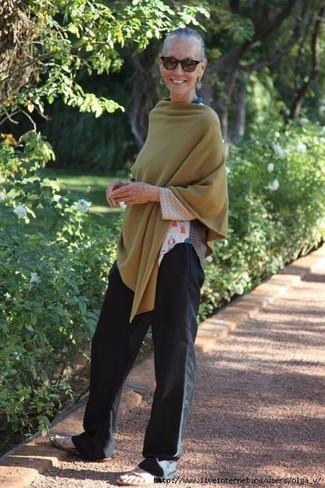 Come indossare: poncho verde oliva, t-shirt manica lunga stampata bianca, pantaloni larghi neri, sandali piatti in pelle beige