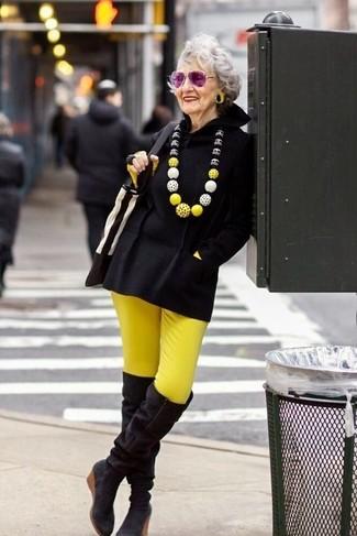 Come indossare e abbinare: poncho nero, t-shirt manica lunga gialla, pantaloni skinny gialli, stivali sopra il ginocchio in pelle scamosciata neri