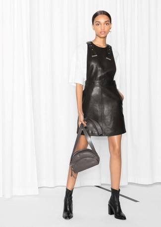 Come indossare: scamiciato in pelle nero, camicetta manica corta bianca, stivaletti in pelle neri, marsupio in pelle grigio scuro