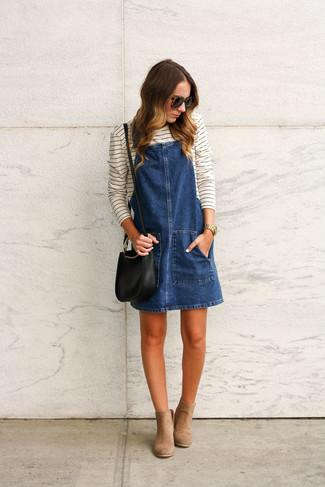 Come indossare: scamiciato di jeans blu scuro, t-shirt manica lunga a righe orizzontali bianca e nera, stivaletti in pelle scamosciata marrone chiaro, borsa a tracolla in pelle nera