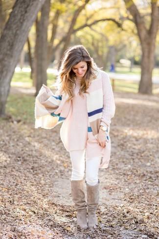 Come indossare e abbinare: scialle a righe orizzontali multicolore, dolcevita lavorato a maglia rosa, jeans aderenti bianchi, stivali al ginocchio in pelle scamosciata beige