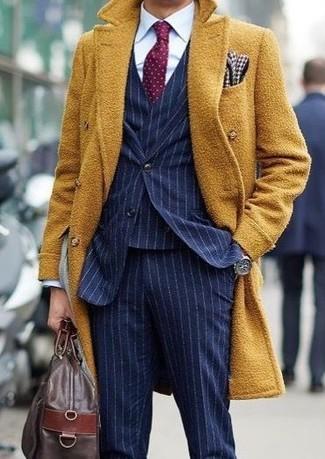 Come indossare e abbinare: soprabito senape, abito a tre pezzi a righe verticali blu scuro, camicia elegante bianca, borsone in pelle marrone scuro