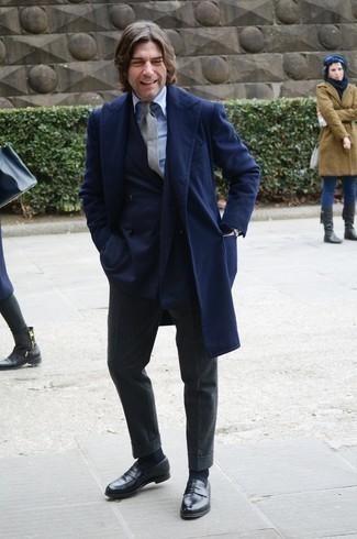 Moda uomo anni 40: Combina un soprabito blu scuro con pantaloni eleganti di lana grigio scuro per un look elegante e alla moda. Mocassini eleganti in pelle neri aggiungono un tocco particolare a un look altrimenti classico.