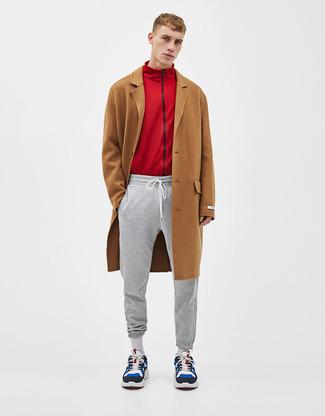 Come indossare e abbinare: soprabito marrone, cardigan con zip rosso, pantaloni sportivi grigi, scarpe sportive in pelle scamosciata multicolori