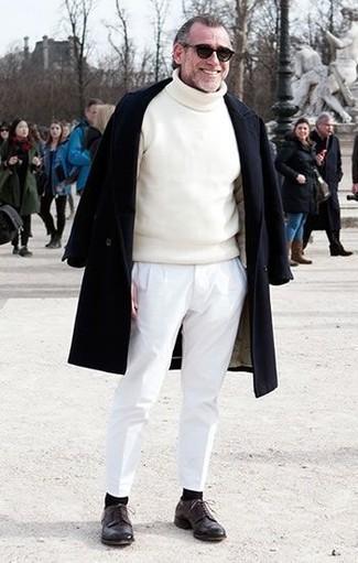 Come indossare e abbinare: soprabito nero, dolcevita bianco, chino bianchi, scarpe derby in pelle marrone scuro