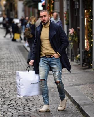 Come indossare e abbinare: soprabito blu scuro, dolcevita di lana marrone chiaro, jeans aderenti strappati blu, stivali chelsea in pelle scamosciata beige