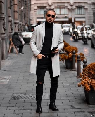 Come indossare e abbinare: soprabito grigio, dolcevita nero, jeans aderenti strappati neri, stivali chelsea in pelle neri