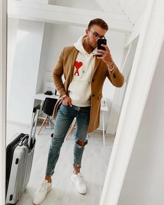 Come indossare e abbinare: soprabito marrone chiaro, felpa con cappuccio stampata bianca, jeans aderenti strappati blu, sneakers basse in pelle bianche
