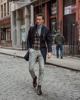 Trend da uomo 2020 quando fa freddo: Coniuga un soprabito nero con chino grigi se preferisci uno stile ordinato e alla moda. Sfodera il gusto per le calzature di lusso e scegli un paio di stivali chelsea in pelle marrone scuro.