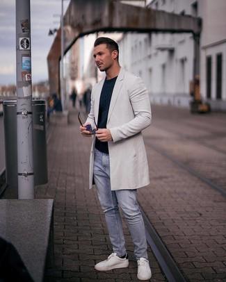 Come indossare e abbinare: soprabito grigio, maglione a trecce blu scuro, jeans strappati azzurri, sneakers basse in pelle bianche