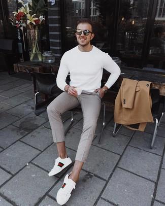 Come indossare e abbinare: soprabito marrone chiaro, maglione girocollo bianco, chino a quadri beige, sneakers basse in pelle stampate bianche