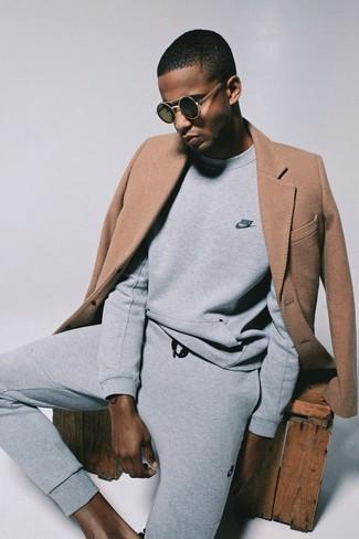 Come indossare: soprabito marrone chiaro, felpa grigia, pantaloni sportivi grigi, occhiali da sole neri