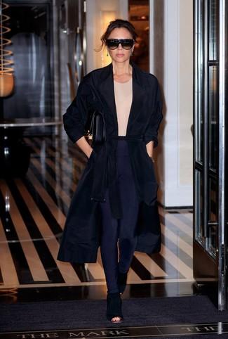 Moda donna anni 40: Per un outfit della massima comodità, indossa uno spolverino nero con leggings blu scuro. Questo outfit si abbina perfettamente a un paio di stivaletti in pelle scamosciata tagliati neri.