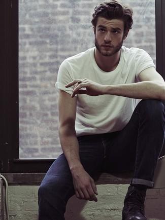 Questa combinazione di una t-shirt girocollo bianca e jeans blu scuro è perfetta per il tempo libero. Completa il tuo abbigliamento con un paio di stivali in pelle neri.