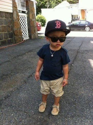 Come indossare e abbinare: t-shirt blu scuro, pantaloncini beige, scarpe da barca marrone chiaro, berretto da baseball nero
