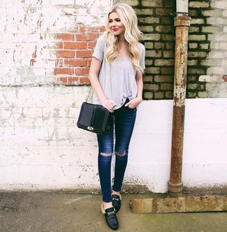 Come indossare e abbinare: t-shirt con scollo a v grigia, jeans aderenti strappati blu scuro, mocassini eleganti in pelle neri, borsa a tracolla in pelle trapuntata nera