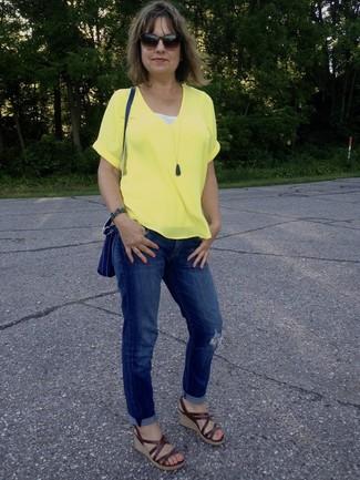 Come indossare: t-shirt con scollo a v gialla, jeans boyfriend strappati blu, sandali con zeppa in pelle marroni, borsa a tracolla in pelle blu