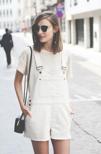 Come indossare e abbinare: t-shirt girocollo a pois bianca e nera, salopette corta bianca, borsa a tracolla in pelle nera