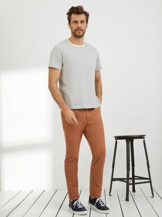 Trend da uomo: Potresti abbinare una t-shirt girocollo a righe orizzontali bianca con chino terracotta per affrontare con facilità la tua giornata. Sneakers basse in pelle nere sono una interessante scelta per completare il look.
