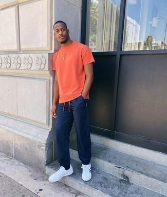 Trend da uomo 2020 in modo rilassato: Abbina una t-shirt girocollo arancione con pantaloni sportivi blu scuro per un look comfy-casual. Sneakers basse in pelle bianche e nere daranno lucentezza a un look discreto.