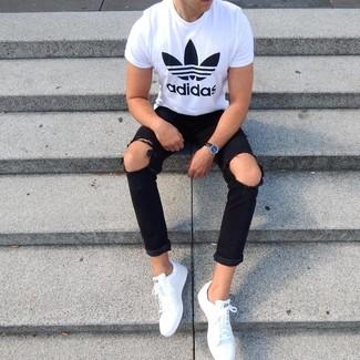 Come indossare e abbinare: t-shirt girocollo stampata bianca e nera, jeans aderenti strappati neri, sneakers basse in pelle bianche, orologio in pelle nero