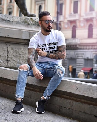 Come indossare e abbinare: t-shirt girocollo stampata bianca e nera, jeans strappati azzurri, scarpe sportive nere, occhiali da sole grigio scuro