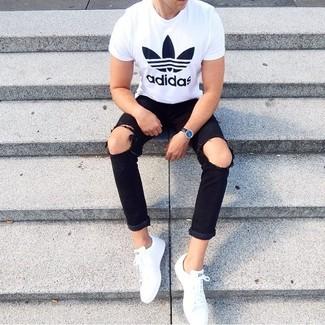 Come indossare e abbinare: t-shirt girocollo stampata bianca e nera, jeans strappati neri, sneakers basse bianche, orologio in pelle nero