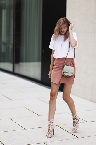 Come indossare e abbinare una minigonna in pelle scamosciata rosa: Vestiti con una t-shirt girocollo bianca e una minigonna in pelle scamosciata rosa per un look facile da indossare. Sandali con tacco in pelle beige sono una eccellente scelta per completare il look.
