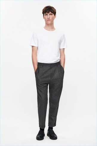 Come indossare: t-shirt girocollo bianca, pantaloni eleganti di lana grigio scuro, sneakers senza lacci in pelle nere, calzini neri
